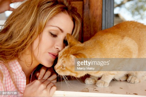 Young woman in pink gingham with orange tabby cat : Stock Photo