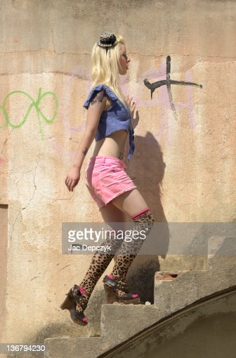 Young woman in pink hot pants climbing staircase : Stock Photo