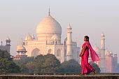 Young woman in pink sari with Taj Mahal in distanc
