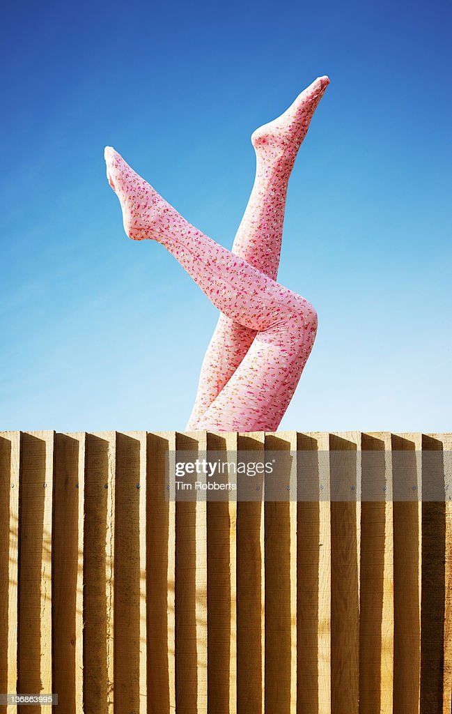 Young woman in pink tights with legs in the air.