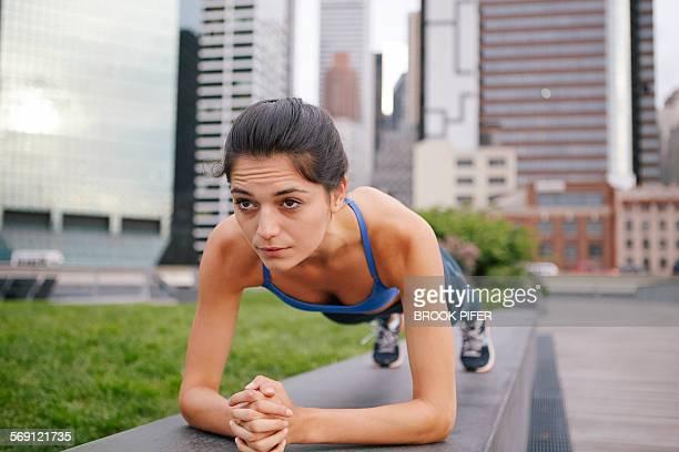 Young woman in plank yoga pose in urban setting