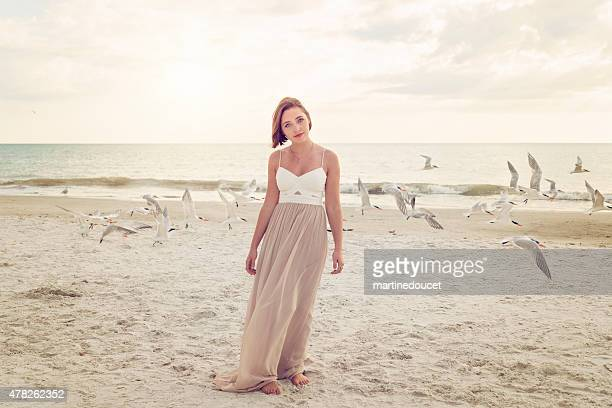 Young woman in prom dress on the beach with birds.