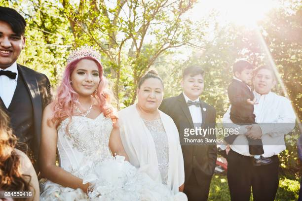 Young woman in quinceanera gown standing with grandmother and family in backyard