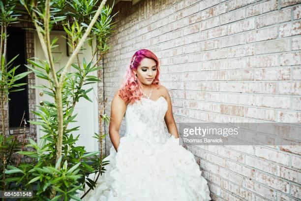Young woman in quinceanera gown walking down front walkway of home