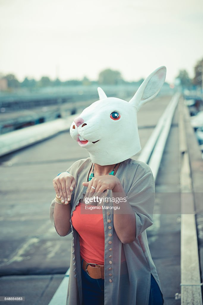 Young woman in rabbit costume mask in city industrial area : Stock Photo