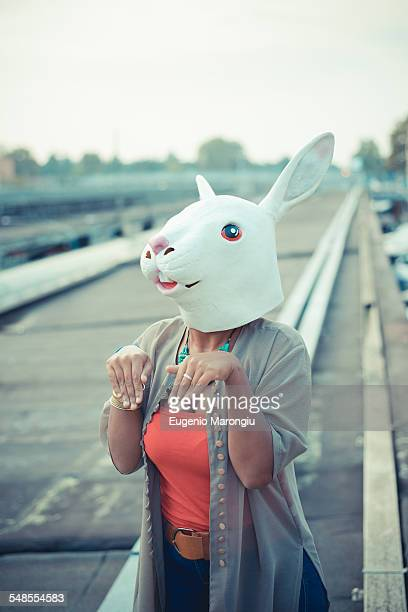 Young woman in rabbit costume mask in city industrial area