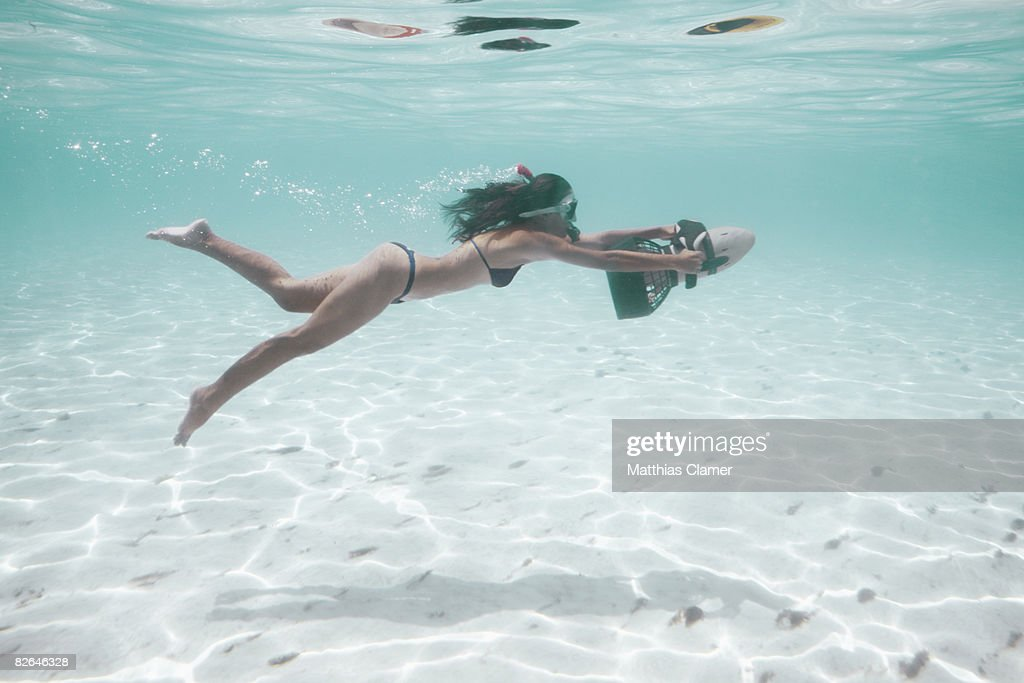 young woman in red bikini is pulled along underwat : Stock Photo