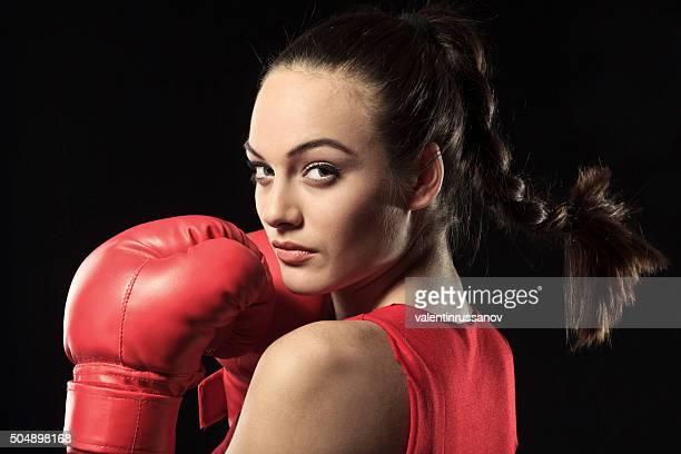 Young Woman in Red Boxing ajuste mirar por encima del hombro