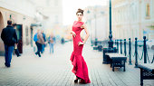 Young woman in red dress on city streets