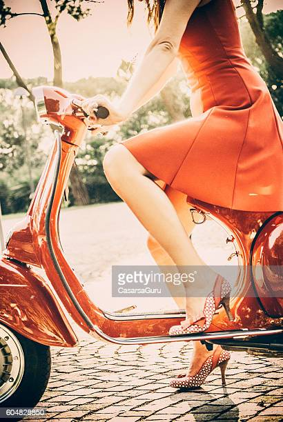 Young Woman In Red Dress Riding a Vintage Scooter