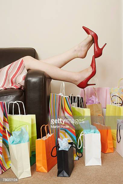 'Young woman in red shoes, lying on sofa surrounded by shopping bags, low section'