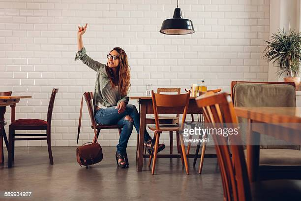 Young woman in restaurant calling for waiter