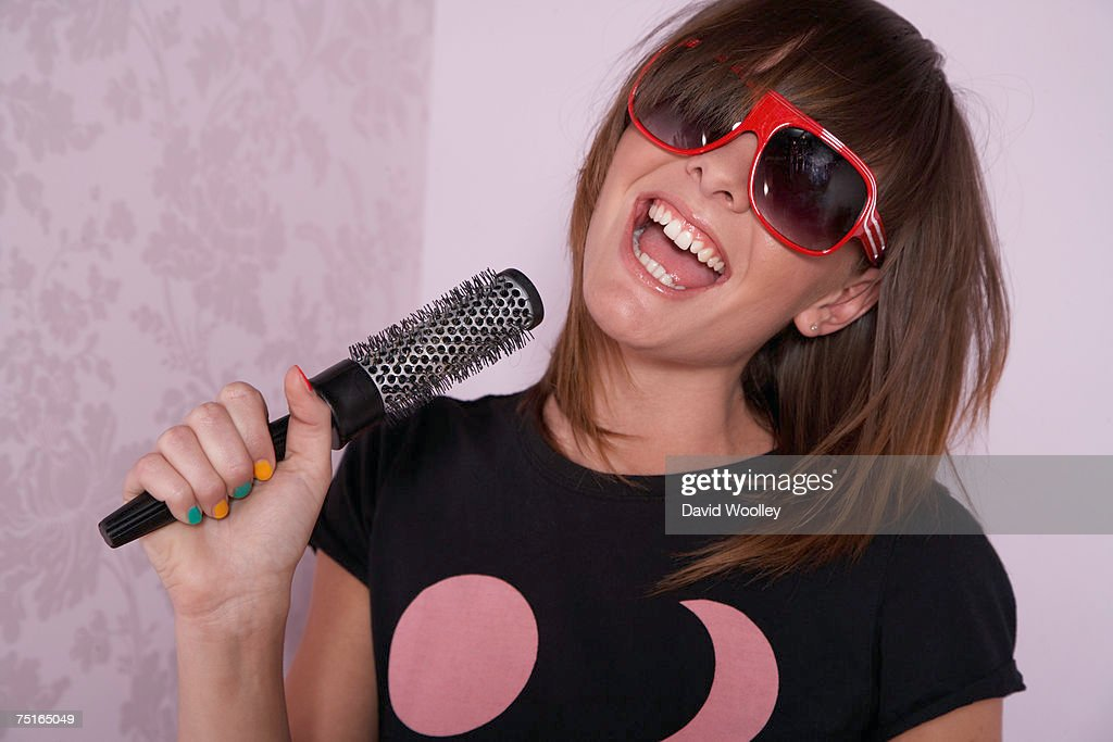 Young woman in room, singing into hairbrush, laughing : Stock Photo