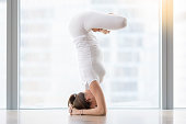 Young woman practicing yoga, standing in salamba sirsasana exercise, headstand with padmasana legs pose, working out, wearing sportswear, white t-shirt, pants, indoor full length, near floor window