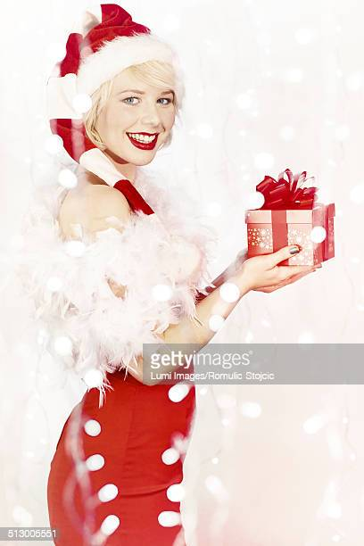 Young woman in Santa Claus costume holding gift box