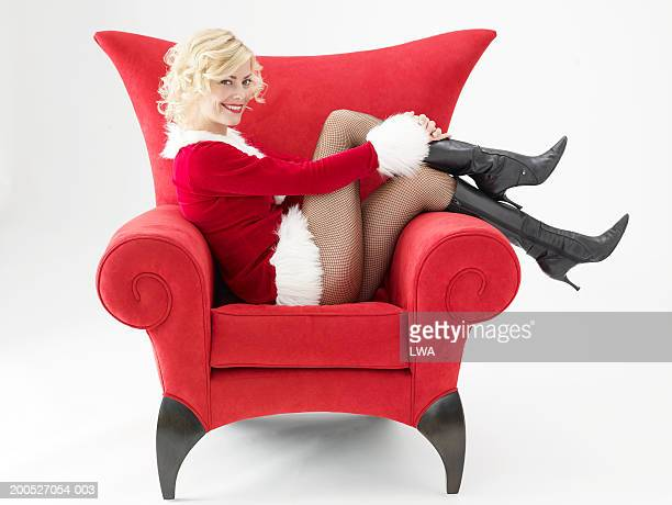Young woman in Santa suit sitting on chair, smiling, portrait