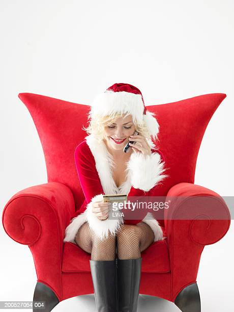 Young woman in Santa suit using mobile phone, holding credit card