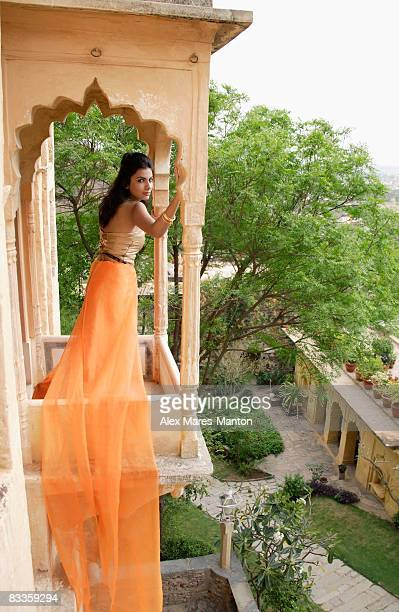 young woman in sari standing at terrace balcony