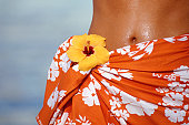 Young woman in sarong, close-up, midsection