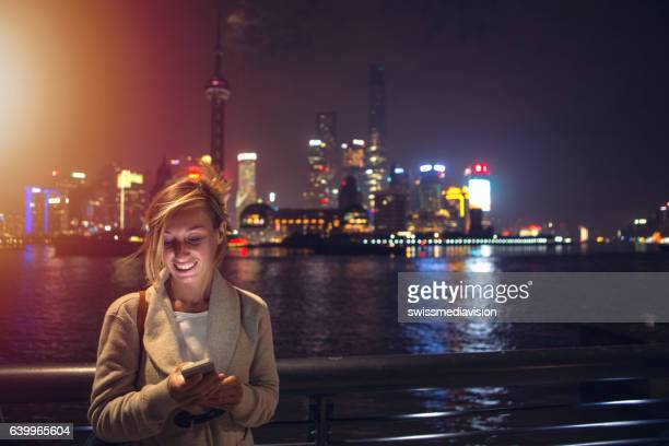 Young woman in Shanghai text messaging on mobile phone, night