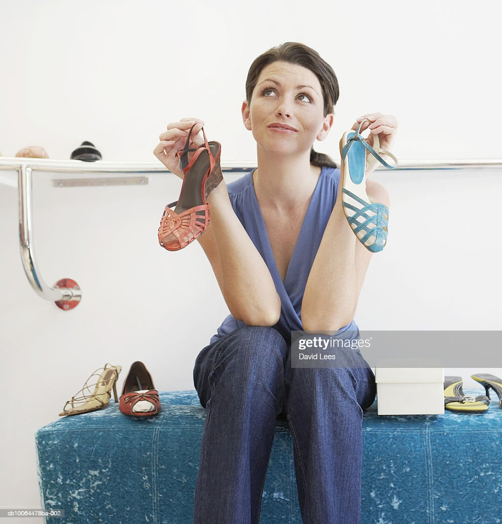 Young woman in shoe shop holding two sandals, looking up : Foto de stock