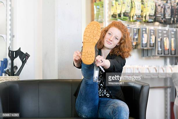 Young woman in shoe shop trying on shoe