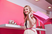 Young woman in shoe store with shopping bag