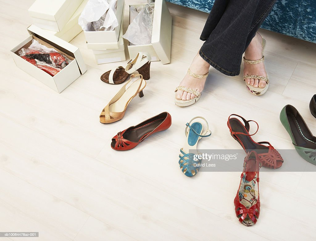 Young woman in shop trying on shoes, low section