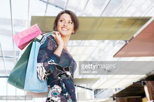 Young woman in shopping mall, holding bags, looking over shoulder : Stock Photo