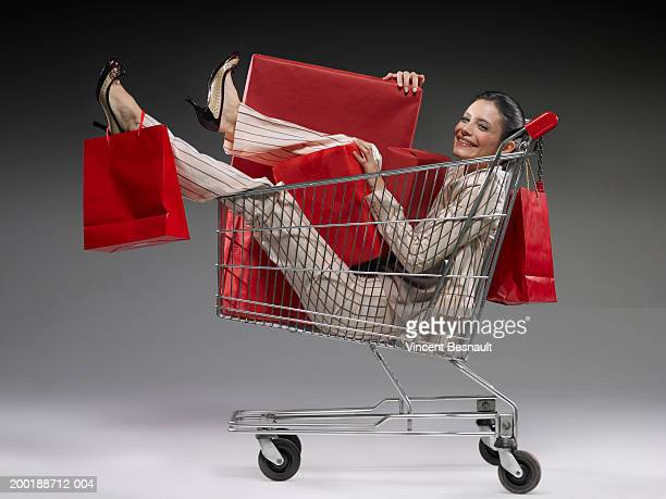 Young woman in shopping trolley full of packages, smiling, portrait