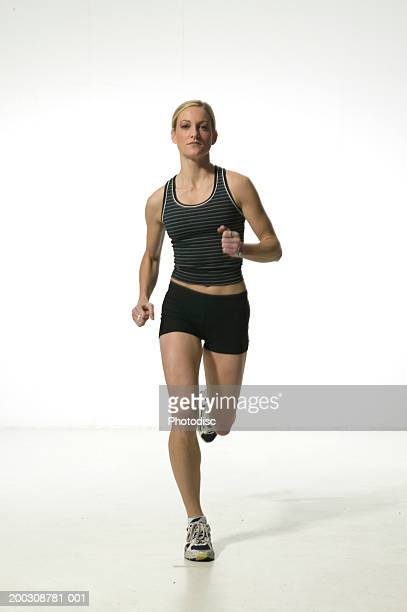 Young woman in shorts and vest,  running, portrait