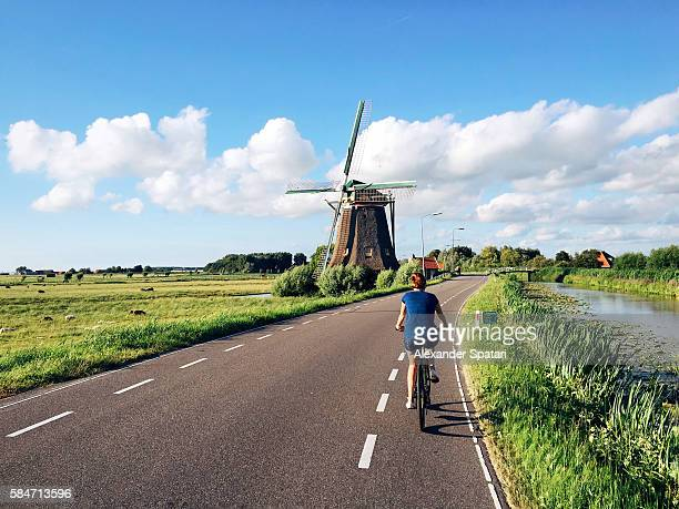 Young woman in shorts riding a bike near traditional Dutch windmill near Maasland, Holland, Netherlands