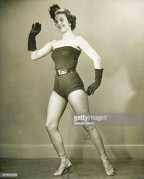 Young woman in showgirl leotards standing in empty room, posing, (B&W)
