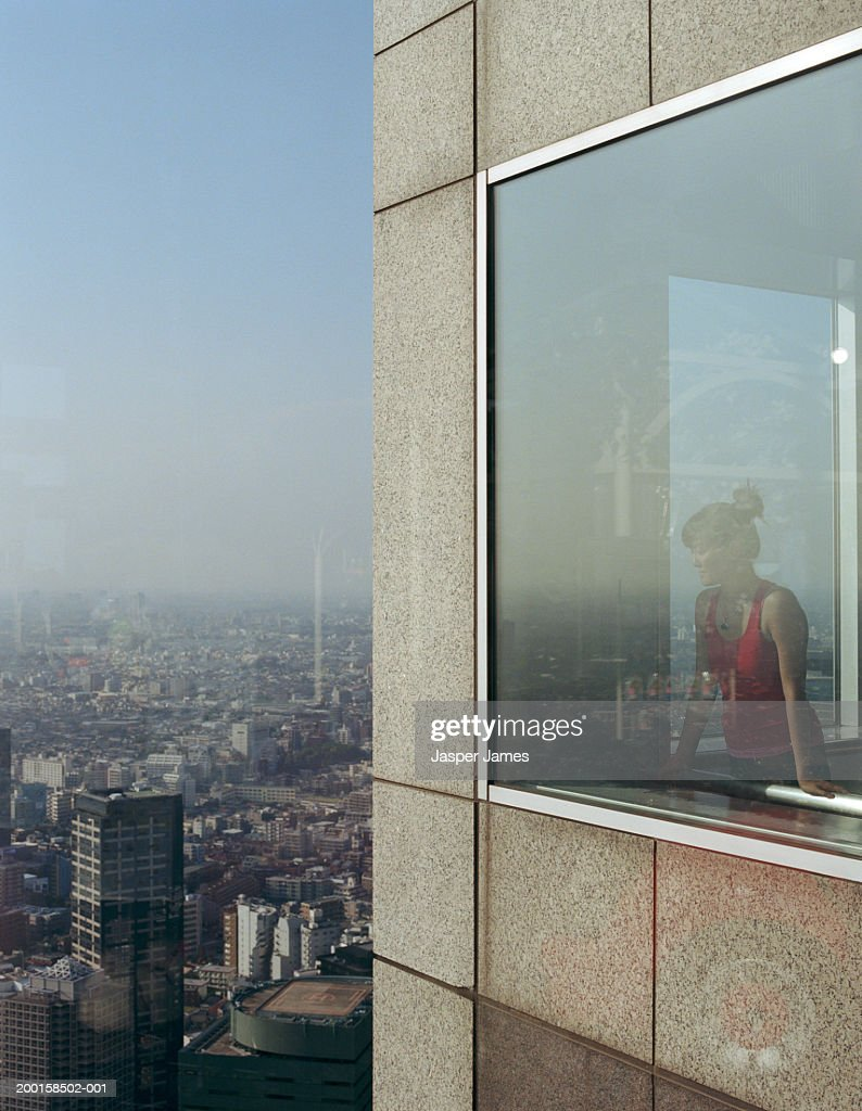Young woman in skyscraper overlooking city, exterior view : Stock Photo