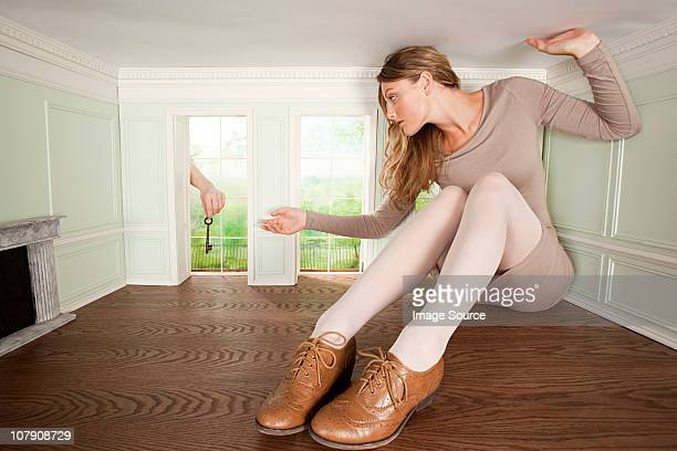 Young woman in small room being handed a key