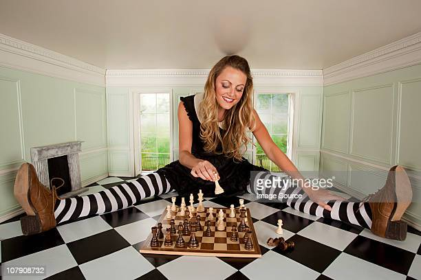 Young woman in small room with chess set