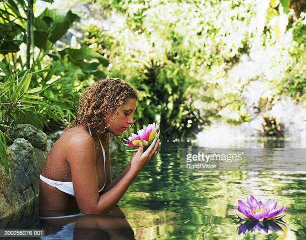 Young woman in spa, smelling water lily, side view
