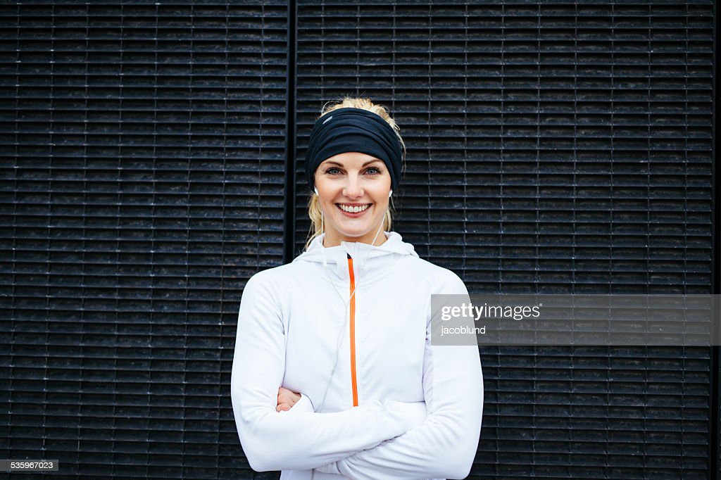 Young woman in sportswear looking at camera smiling : Stock Photo