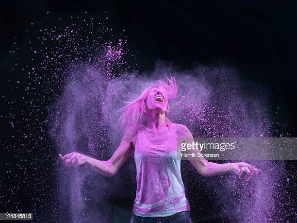 Young woman in spray of colored powder