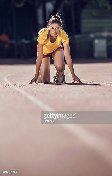 Young woman in starting position ready for running.