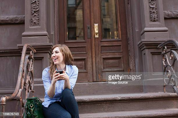 Young woman in steps of building with cellphone