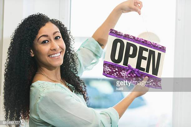 Young woman  in store holding open sign