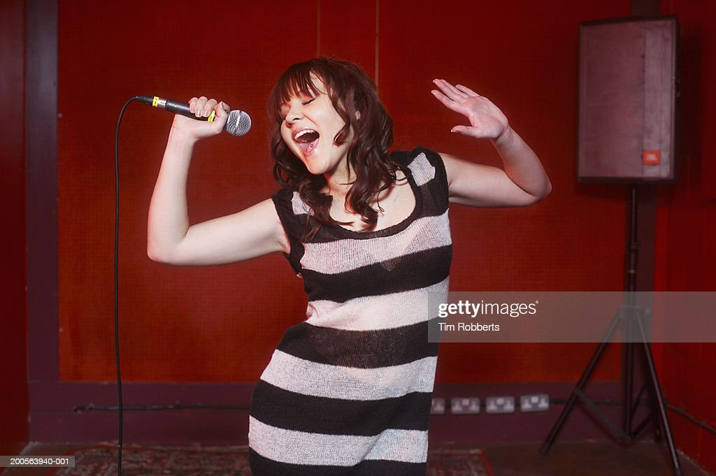 Young woman in striped dress singing into microphone on stage : Stock Photo