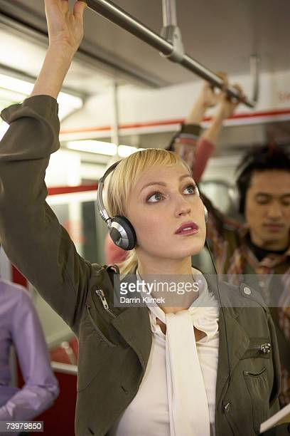 Young woman in subway train, wearing headphones, holding onto railings