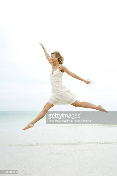 Young woman in sundress jumping in the air, ocean horizon in background, arms out, side view