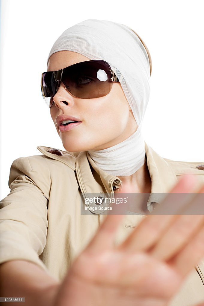 Young woman in sunglasses and bandages after cosmetic surgery : Stock Photo