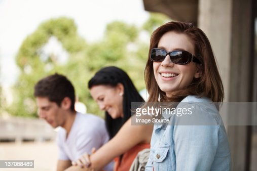 Young woman in sunglasses smiling at the camera : Stock Photo
