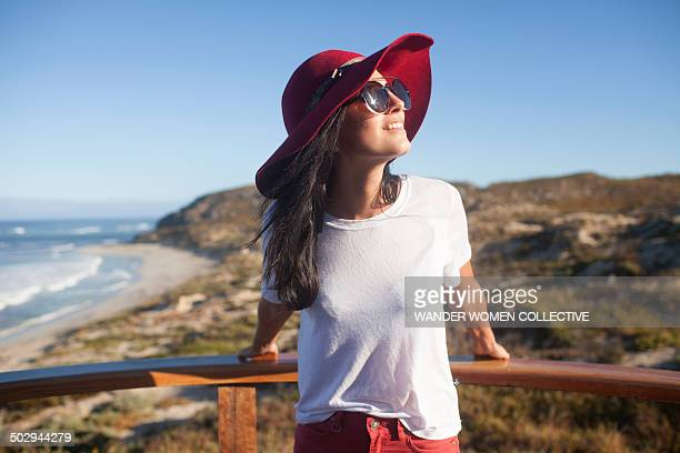 Young woman in sunhat at beach lookout Australia