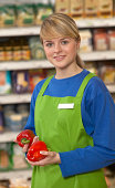 Young woman in supermarket holding red peppers, smiling, portrait