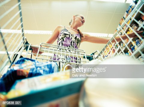 Young woman in supermarket, low angle view : Stock Photo
